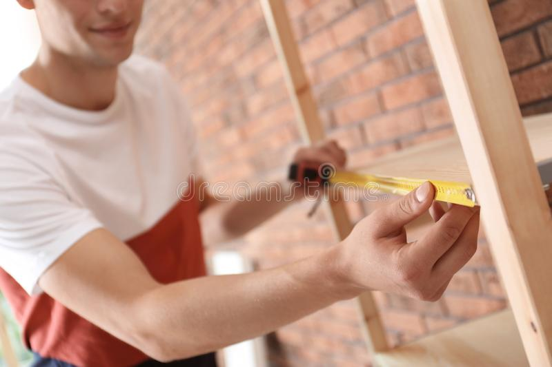 Young working man measuring wooden shelf indoors royalty free stock photography