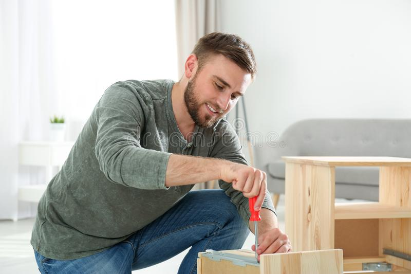 Young working man repairing drawer at stock photography