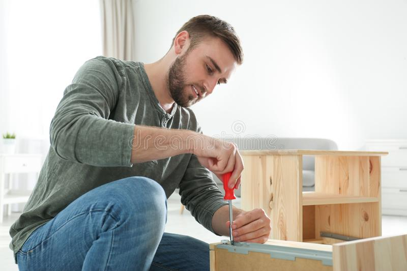 Young working man repairing drawer stock photo
