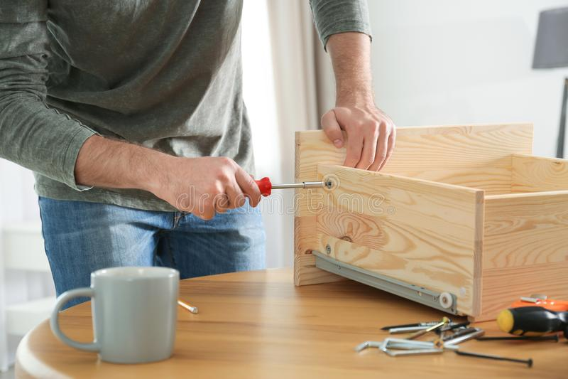 Young working man repairing drawer at home stock images