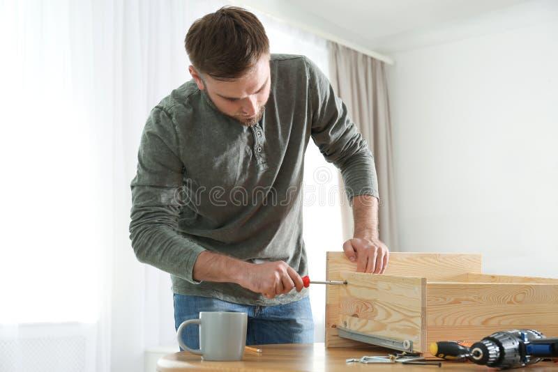 Young working man repairing drawer royalty free stock image