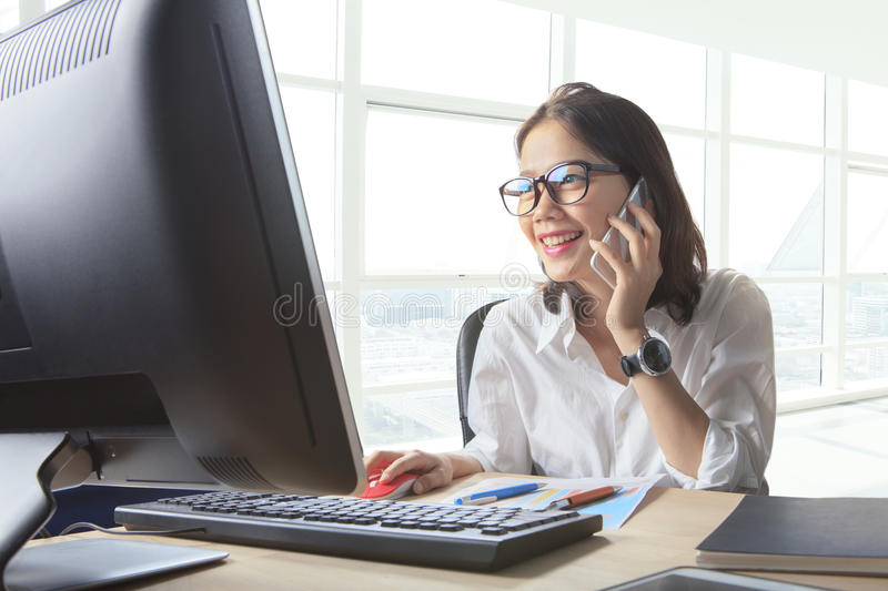 Young working woman talking to phone with watching on computer o. N office table use for business connecting ,customer service ,communication stock photography