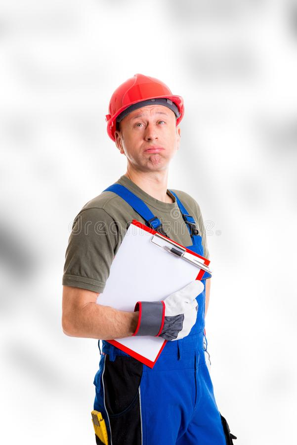 Workman in blue dungarees with clipboard looking sceptical stock photo