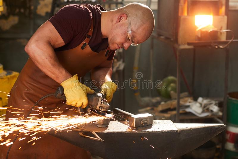 Young workman polishing metal with grinder royalty free stock photography