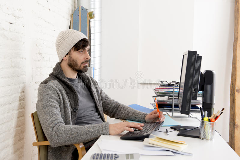 Young worried businessman in cool hipster beanie look looking desperate having problem working in stress. At home office with computer in business frustration royalty free stock images