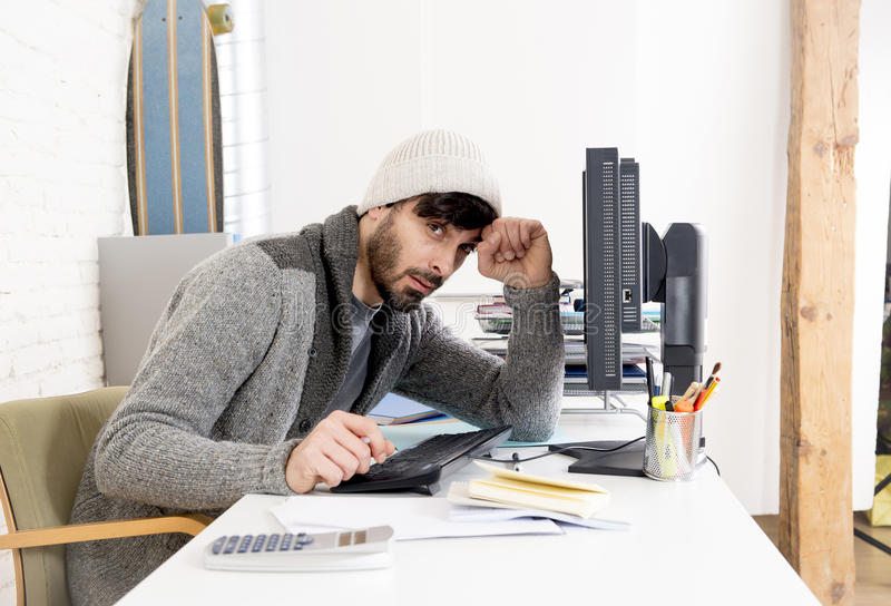 Young worried businessman in cool hipster beanie look looking desperate having problem working in stress. At home office with computer in business frustration royalty free stock image