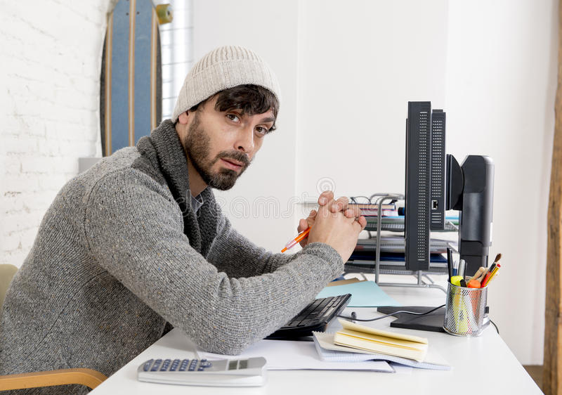 Young worried businessman in cool hipster beanie look looking desperate having problem working in stress. At home office with computer in business frustration royalty free stock photos