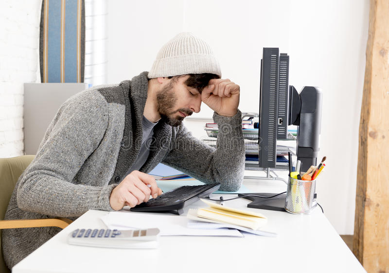 Young worried businessman in cool hipster beanie look looking desperate having problem working in stress. At home office with computer in business frustration stock photography