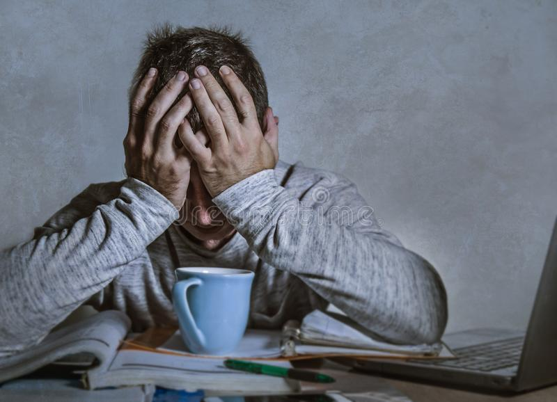Young worried and depressed man working late night at home desk with laptop computer feeling frustrated and tired accounting paper royalty free stock photography
