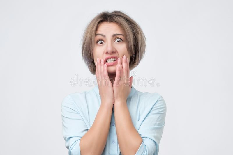 Young worried woman in desperate situation holding hands on head. stock image