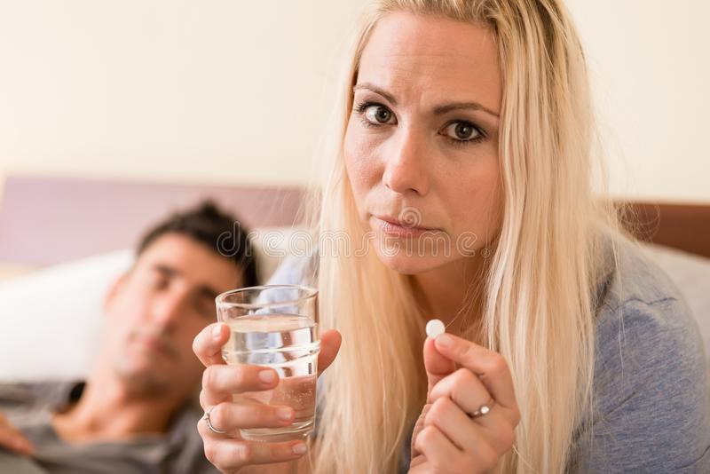 Worried woman taking a pill before sleep at night. Young worried women sitting in bed next to her partner while taking a pill before sleep at night stock images
