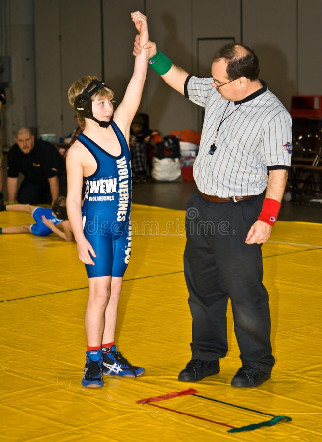 Young Wrestler Winner. A referee raising a boy's arm, showing that he won his wrestling match. This took place at the Dixie Nationals Championship in Atlanta GA royalty free stock photo