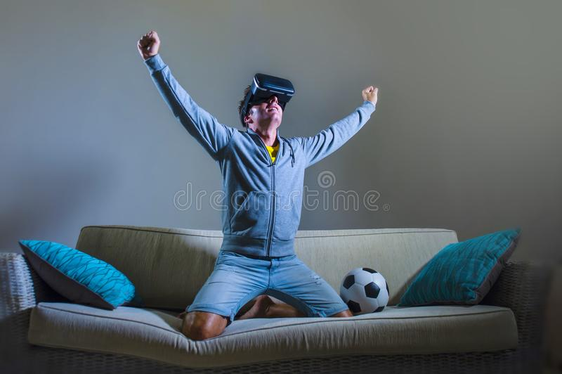 Young xcited gamer man using VR virtual reality goggles headgear playing football simulation game celebrating scoring goal at home. Young happy and excited gamer stock photography