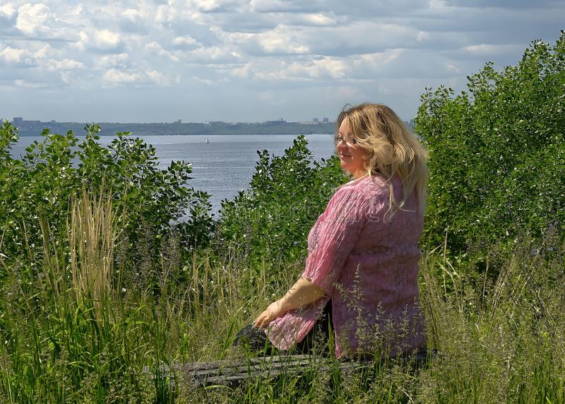 A young 40 years old fat woman sits on a bench in a clearing above the Volga River Russia stock photo