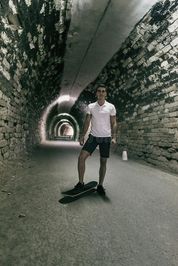 Young 20-25 years old man in tunnel with skateboard. Ambient light image (IMAGE HAVE SOME NOISE). Young 20-25 years old man in tunnel with skateboard. Ambient royalty free stock photos