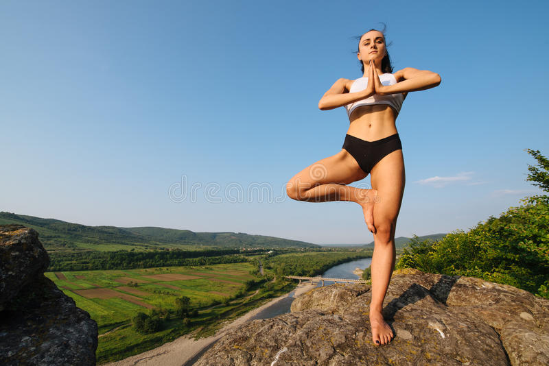 Young yoga woman with perfect muscular body doing tree pose. Meditation and balance exercise in wonderful nature. Mountain landscape royalty free stock photos
