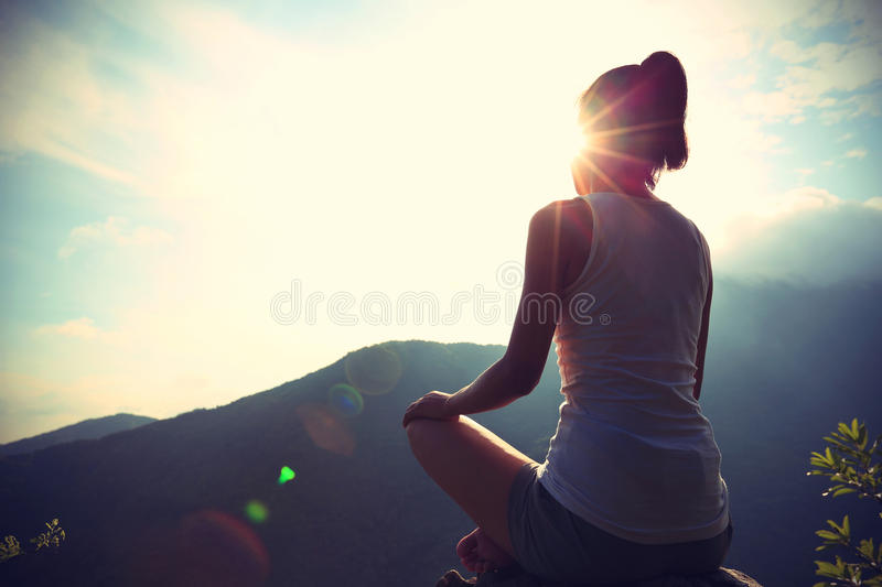 Young yoga woman at sunrise mountain stock photography