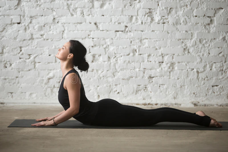 Young yogi attractive woman in Cobra pose, white loft background royalty free stock photos