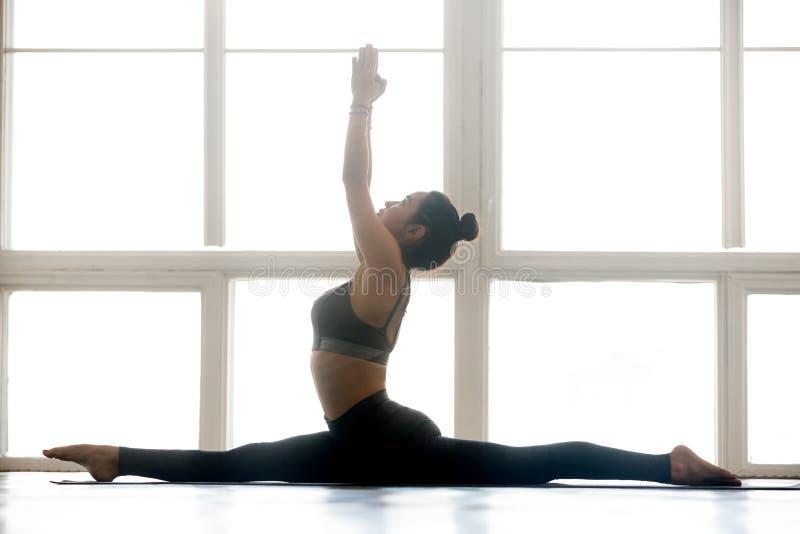 Young yogi attractive woman practicing yoga, doing Hanumanasana. Young yogi attractive woman practicing yoga, doing Monkey God exercise, Splits, Hanumanasana royalty free stock photo