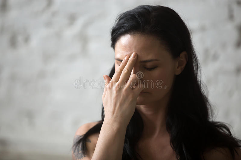 Young yogi attractive woman using Alternate Nostril Breathing yo. Middle aged yogi attractive woman practicing yoga concept, making Alternate Nostril Breathing stock photography