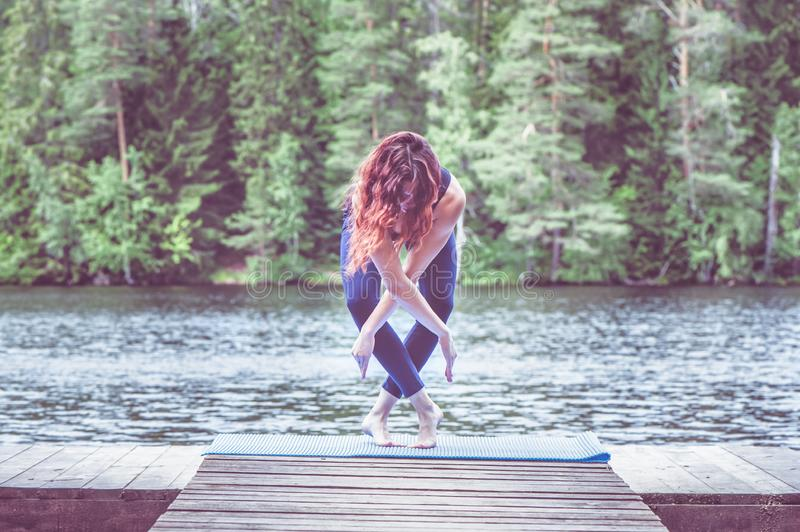Young yogi  girl  on the pier of a beautiful lake.  Concept of healthy life and natural balance stock image
