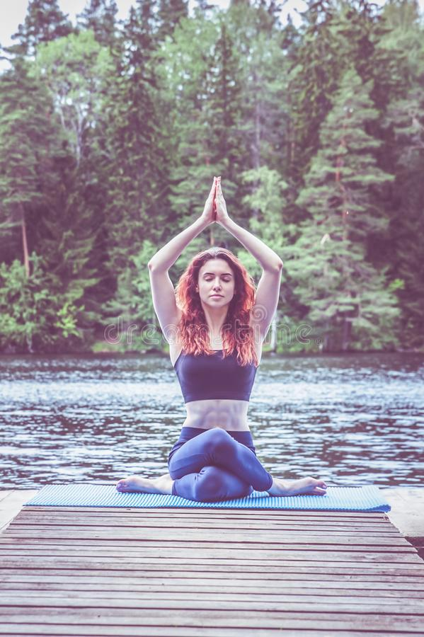 Yogi  girl  practicing yoga, sitting in variation of Gomukhasana, Cow Face Posture  on the pier of a beautiful lake. Concept. Young yogi  girl  practicing yoga royalty free stock photos