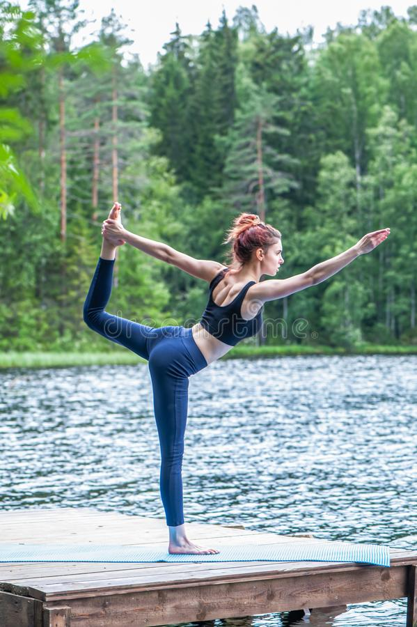 yogi  girl  practicing yoga, variation of Natarajasana, Lord of the Dance Pose on the lake.  Concept of healthy life and stock photo