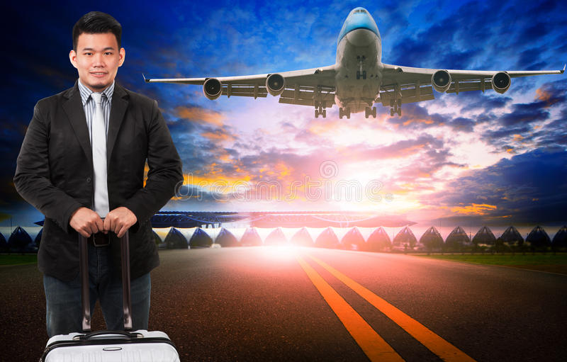 younger asian man and traveling luggage standing against passenger plane flying over airport runway stock photos