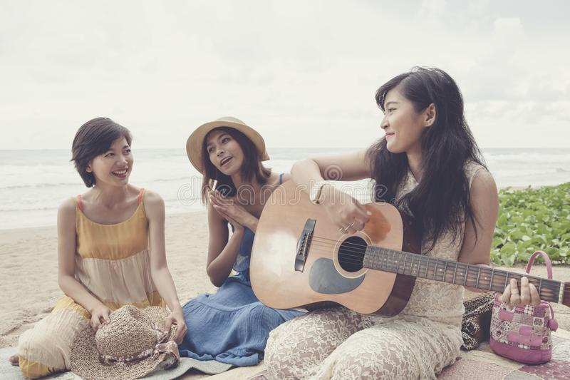 Younger asian woman friend vacation relaxing playing guitar and stock photos