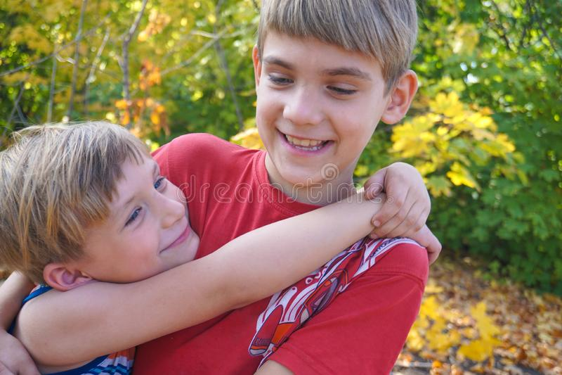 The younger brother hugs the older one and looks at him, two loving brothers are standing in an embrace in the park against the. Background of autumn leaves stock photography