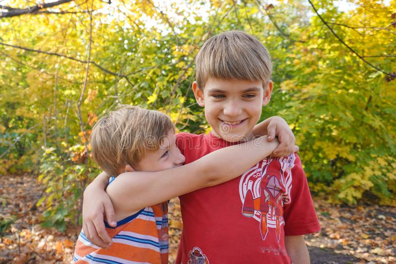 The younger brother hugs the older one and looks at him, two loving brothers are standing in an embrace in the park against the. Background of autumn leaves royalty free stock images