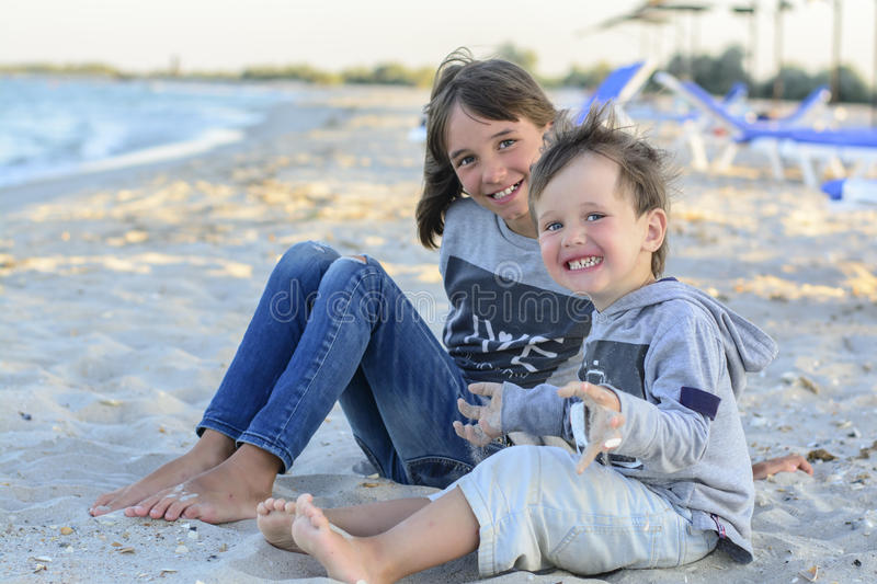 The younger brother and sister sitting on the beach and having fun, sunset.  royalty free stock photo