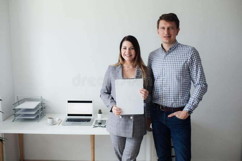 Younger girl and man working in the office at the table royalty free stock image