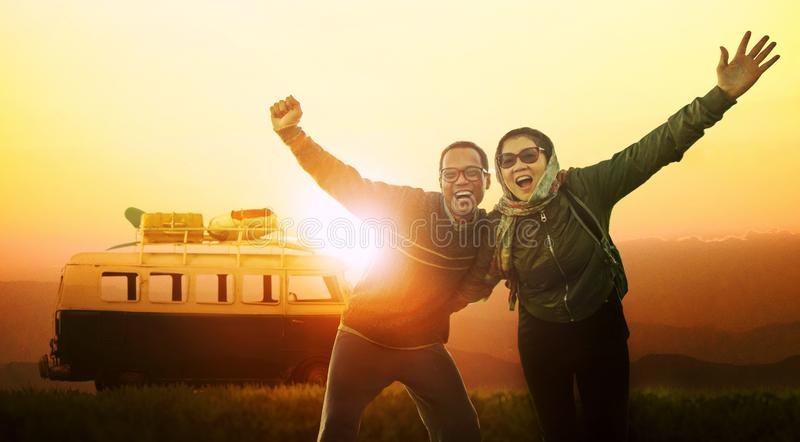 Younger man and woman happiness emotion traveling to destination against beautiful sun set sky royalty free stock photo