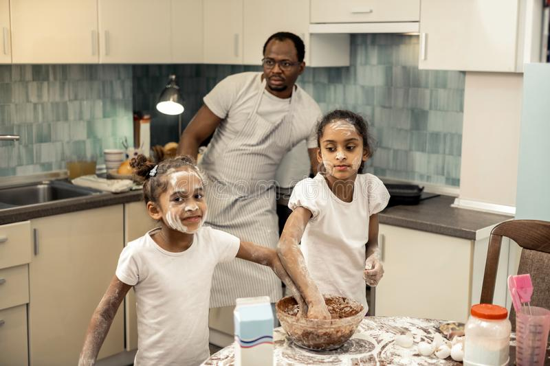 Younger and older sisters feeling joyful while cooking together. Younger and older. Younger and older sisters feeling truly happy and joyful while cooking royalty free stock photo