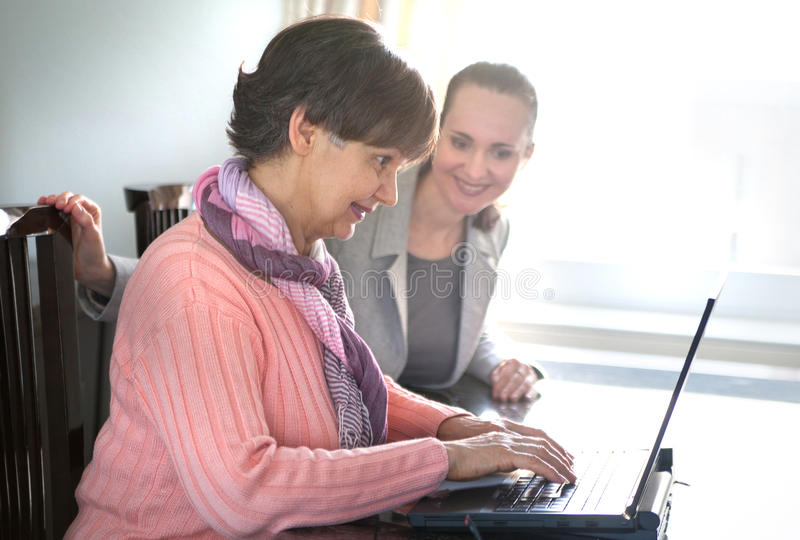 Younger woman helping an elderly person using laptop royalty free stock photos
