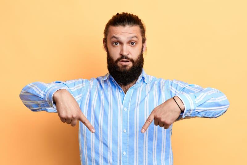 Younghandsome-Mannpunkt mit den Zeigefingern unten stockfoto