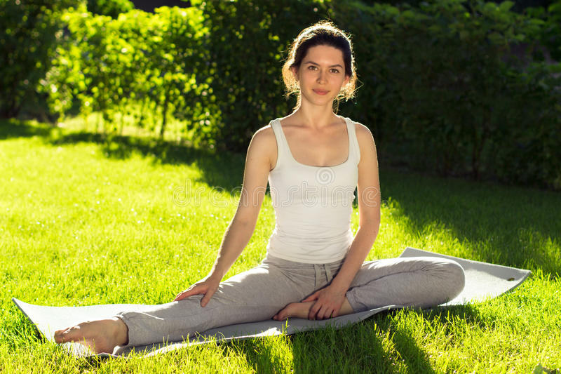 Youngl woman doing yoga in the park in the morning stock image