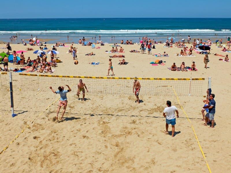 Youngsmäns spela volleyboll i den Zurriola stranden, San Sebastian spain royaltyfria bilder