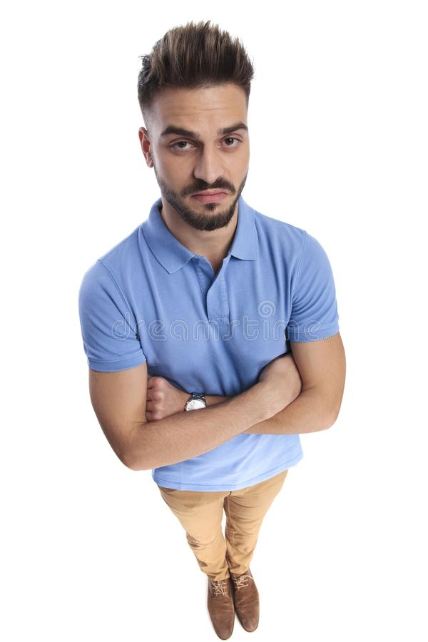 Youngster man wearing a light blue polo. Holding his hand crossed while looking upwards at the camera stock photography