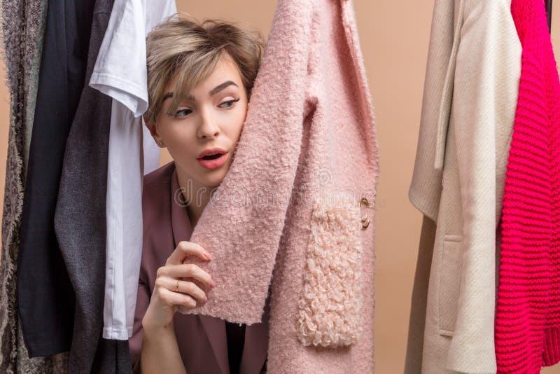 Youngwoman espiègle de charme jouant le cache-cache avec quelqu'un image stock