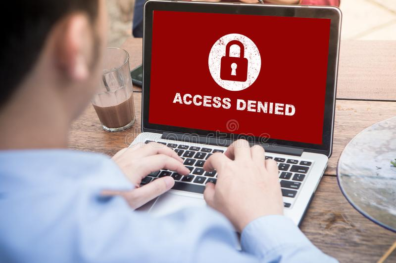 Your access is denied on laptop screen concept, protection security system. Protection security system concept. Man working on laptop with access denied text on stock photo