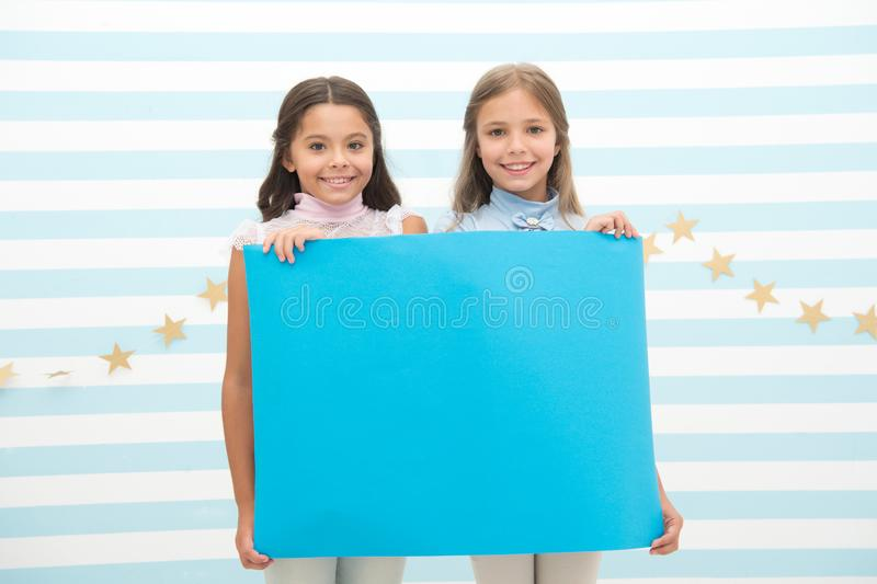 Your advertisement in good hands. Girls kids hold advertisement poster copy space. Children hold advertising banner. Happy children with blank paper for stock photos