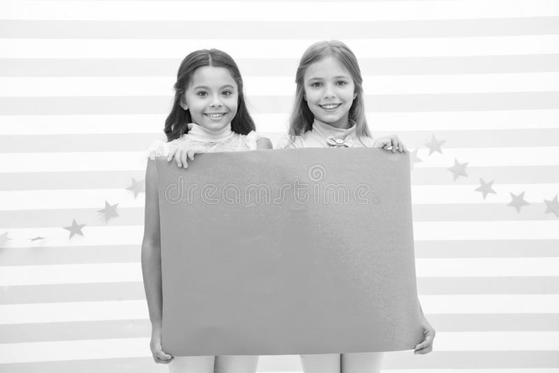 Your advertisement in good hands. Girls kids hold advertisement poster copy space. Children hold advertising banner. Happy children with blank paper for royalty free stock image