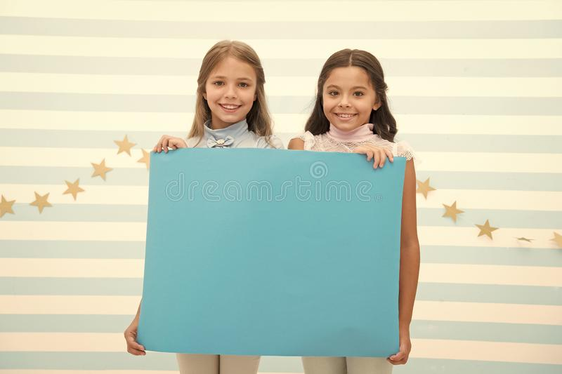 Your advertisement in good hands. Girls kids hold advertisement poster copy space. Children hold advertising banner. Happy children with blank paper for royalty free stock images