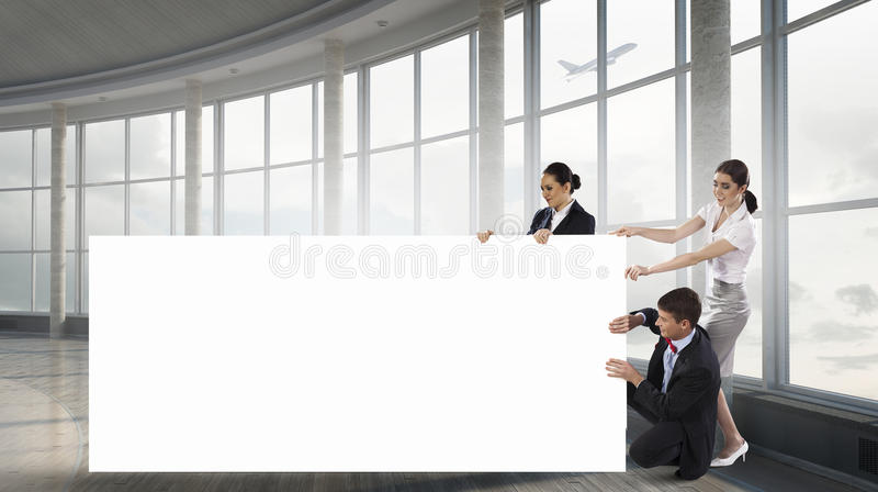 Your advertisement in good hands. Group of young business people holding big blank banner. Mixed media stock photos