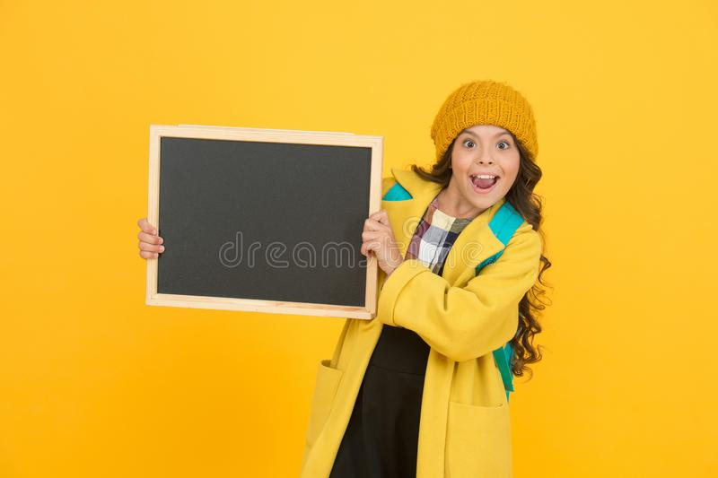 Your advertising gets on top. Happy small child hold advertising board yellow background. Little girl advertising stock photography