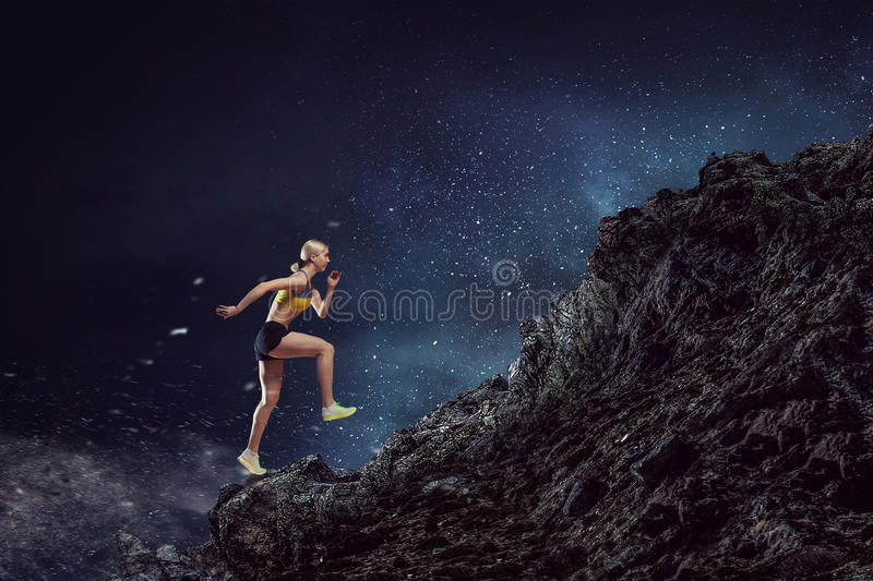 Your best motivation. Mixed media. Young woman athlete running fast on dark background. Mixed media stock photos