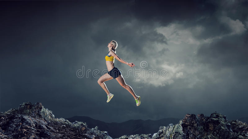 Your best motivation. Mixed media. Young woman athlete running fast on dark background. Mixed media stock images