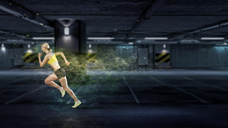 Your best motivation. Mixed media. Young woman athlete running fast on dark background. Mixed media royalty free stock photography